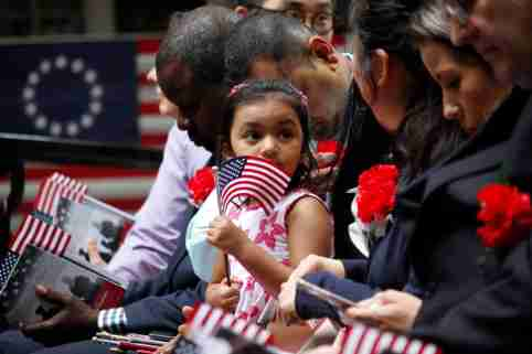 Philadelphia, PA / USA - June 14, 2019: The daughter of a immigrant holds an American flag while she joins her mother's naturalization ceremony on Flag Day at the historic Betsy Ross House. Jana Shea / Shutterstock.com