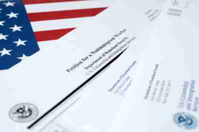 I-129 Petition for a nonimmigrant worker blank form lies on United States flag with envelope from Department of Homeland Security close up