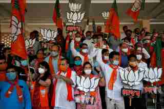 Supporters of India's ruling Bharatiya Janata Party (BJP) hold their party symbols and flags as they gather to celebrate after learning of the initial poll results of the Bihar state assembly election and by-elections in Gujarat, Karnataka and Madhya Pradesh states, in Gandhinagar, India, November 10, 2020. REUTERS/Amit Dave - RC2C0K98BBEN