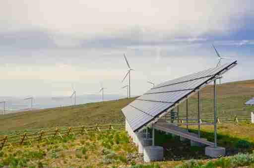 Solar panel and row of wind turbines under cloud blue sky at Ellensburg, Washington, US.