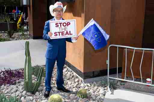 """A supporter of President Donald Trump hold a sign reading """"Stop the steal"""" while protesting against Trump's loss in the 2020 election."""