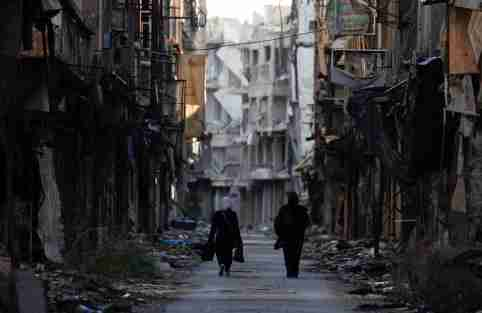 Women walk past damaged buildings at the Yarmouk Palestinian refugee camp on the southern outskirts of Damascus, Syria December 1, 2020. Picture taken December 1, 2020. REUTERS/Omar Sanadiki