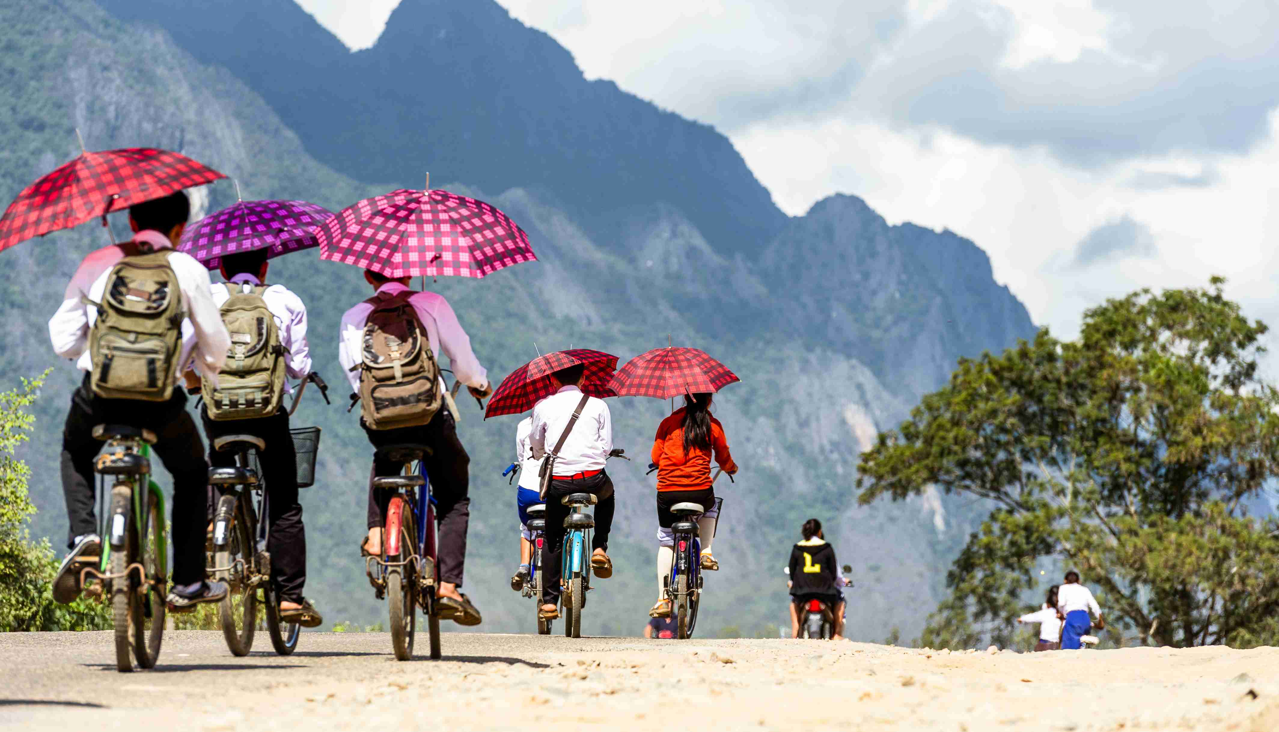 Vang Vieng. Laos. 15/12/2017. Children leaving school by bicycle