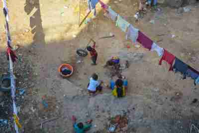 Antananarivo, Madagascar, Africa -January 11 2020: An aerial view of a group of poor children in a slum of the madagascan city. Malagasy kids play with tires in the dirt, surrounded by hanging laundry