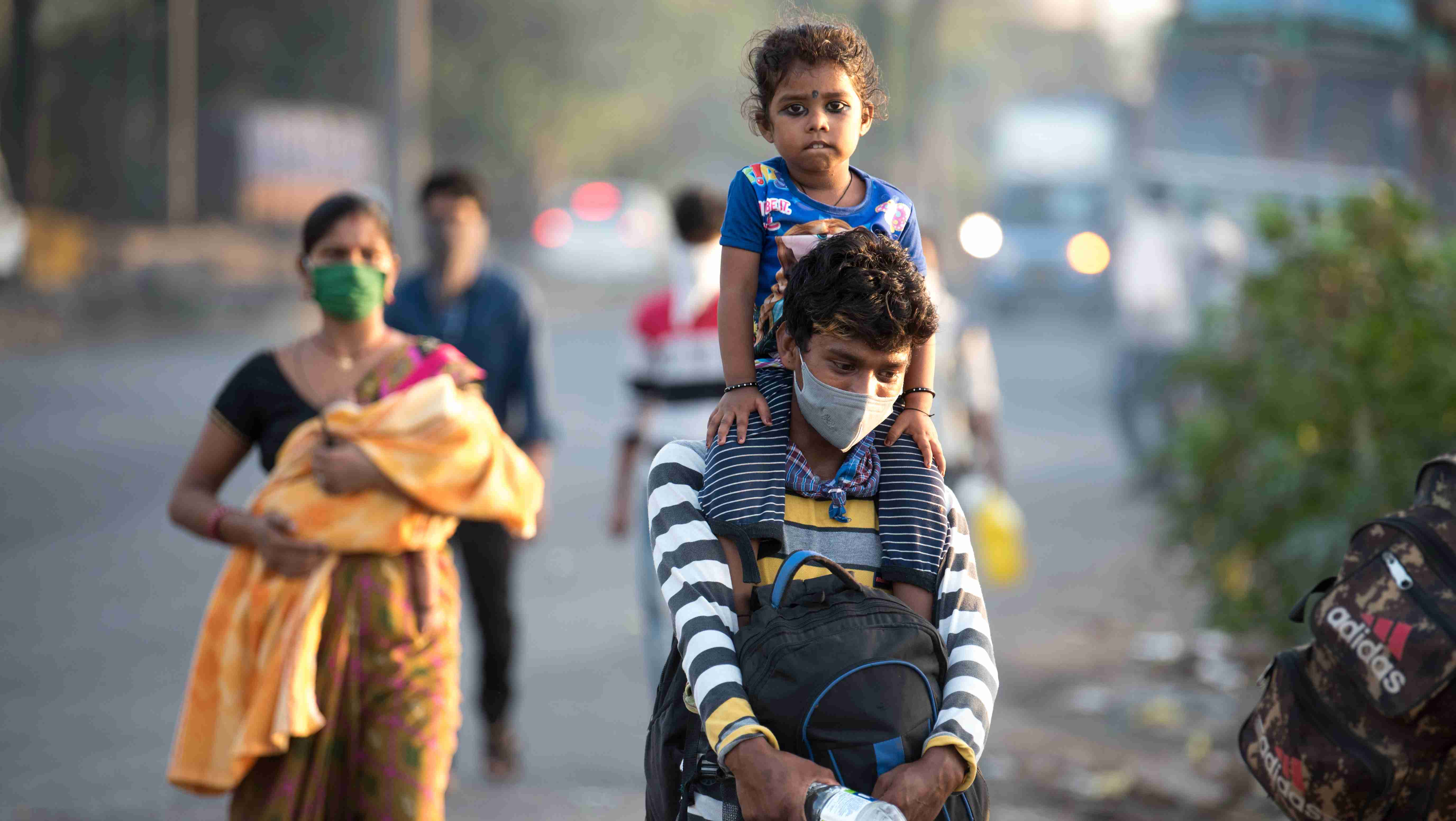 MUMBAI/INDIA - MAY 11, 2020: Migrant workers walk on the highway on their journey back home during a nationwide lockdown to fight the spread of the COVID-19 coronavirus.