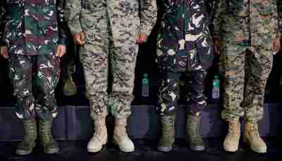The various boots worn by multi-nation troops are seen as the soldiers listen to U.S. President Barack Obama speak to military troops at the Fort Bonifacio Gymnasium in Manila, April 29, 2014. REUTERS/Larry Downing (PHILIPPINES - Tags: POLITICS)