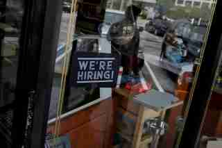 "FILE PHOTO: A ""We're Hiring"" sign advertising jobs is seen at the entrance of a restaurant in Miami, Florida, U.S., May 18, 2020. REUTERS/Marco Bello/File Photo"