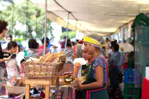 Lima, Peru - February 16 2019: Female worker at bakery selling bread at street market called bioferia in parque reducto, Miraflores