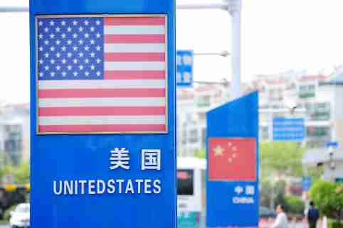 Signboards showing the flags of the United States and China are seen on a street in Qingdao, China.
