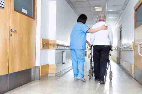 Nurse helping an older person in a nursing home hallway.