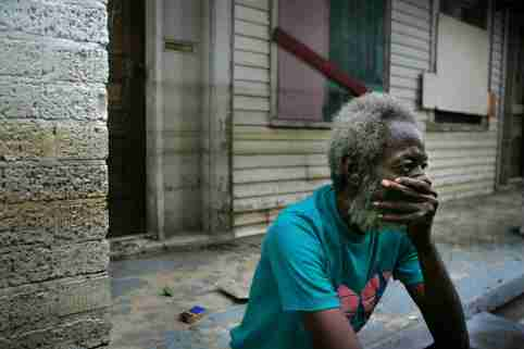 Hurricane Katrina holdout Creek sits on the porch of his house in front of the Memorial Medical Center of New Orleans.  Hurricane Katrina holdout Joshua Creek sits on the porch of his house in front of the Memorial Medical Center of New Orleans September 13, 2005. The discovery of at least 44 bodies in an abandoned hospital in New Orleans raised new questions about the response to Hurricane Katrina on Tuesday as President George W. Bush took full responsibility for government failures in handling the disaster. Pictures of the Year 2005 REUTERS/Carlos Barria
