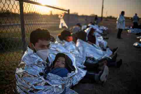 Dustin, an asylum-seeking migrant from Honduras, holds his six-year-old son Jerrardo, 6, as they awake at sunrise next to others who took refuge near a baseball field after crossing the Rio Grande river into the United States from Mexico on rafts, in La Joya, Texas, U.S., March 19, 2021. Emergency blankets were provided to the group of about 150 migrants from Central America by the U.S. Border Patrol agents. REUTERS/Adrees Latif     TPX IMAGES OF THE DAY