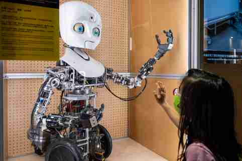 A young girl puts her hand up to a robot with a humanoid face and arm.