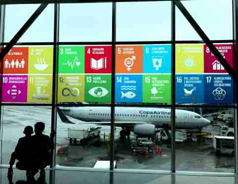Panama City/Panama, October 18, 2018: The Global Goals displayed in Spanish on the windows at Panama City Tocumen International Airport. Mother and child looking out to see the planes.