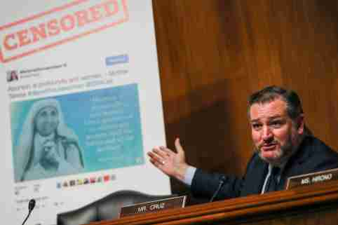 """Sen. Ted Cruz gestures at a poster of a Facebook post depicting the Mother Teresa below a headline reading """"CENSORED."""""""