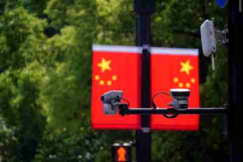 Surveillance cameras are seen mounted in front of two Chinese flags.