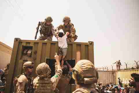 British, Turkish and US soldiers assist a child during the evacuation of civilians at Hamid Karzai International Airport.