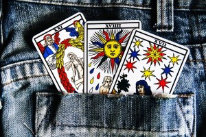 3 marseilles tarot cards fanned out in the pocket of denim jeans