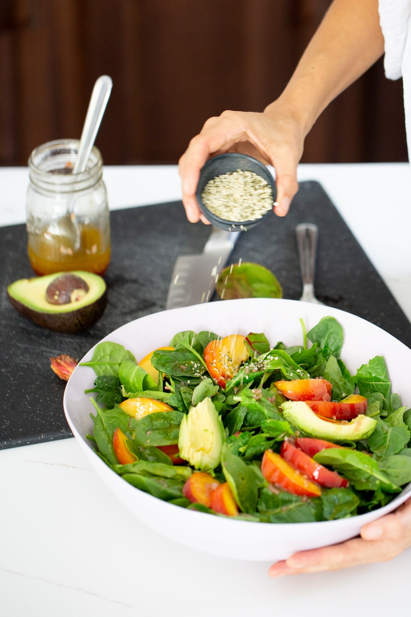 finishing up a peach and avocado summer salad