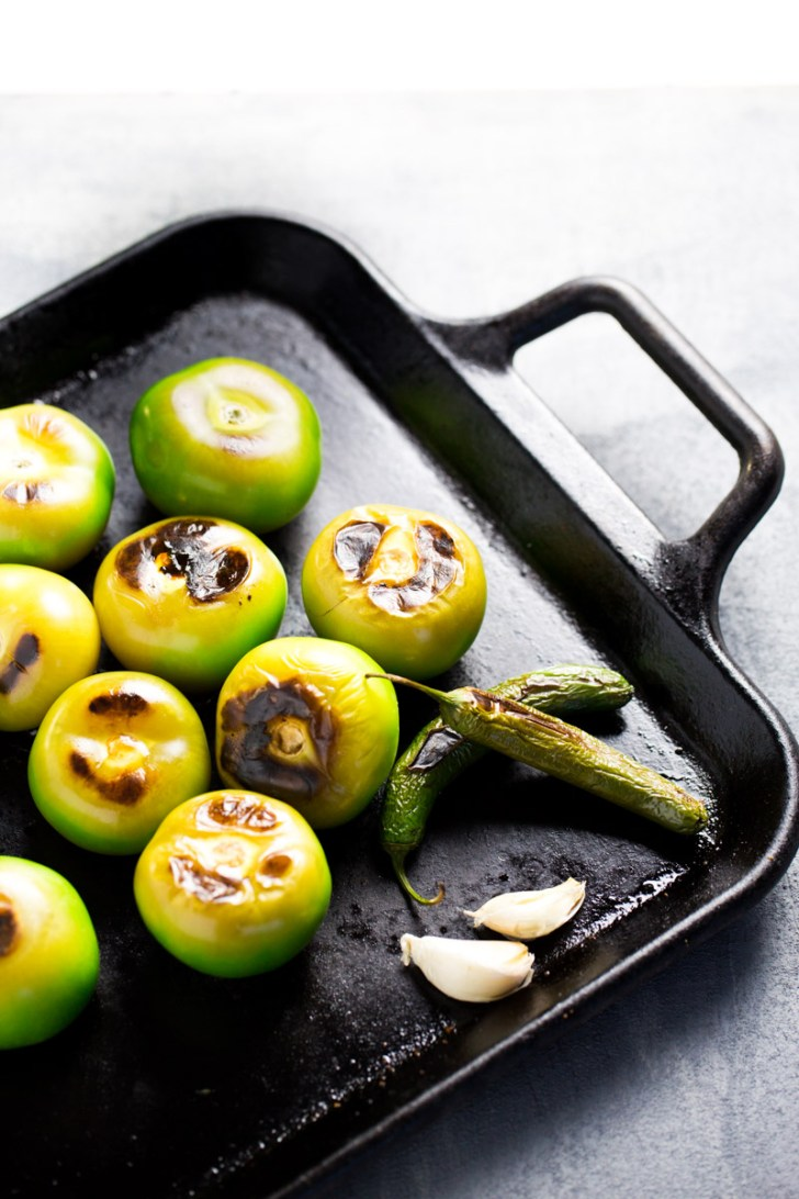 roasted tomatillos , garlic and serrano peppers on a griddle
