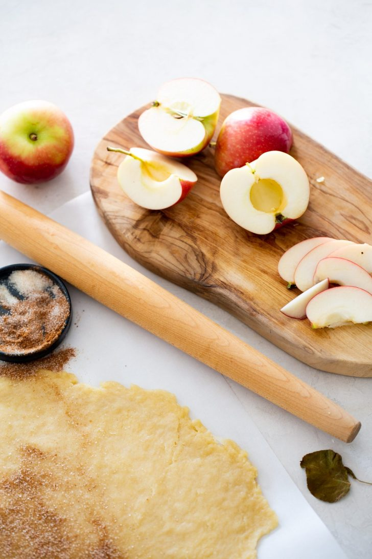 cut apples and rolled dough to prepare the vegan galette