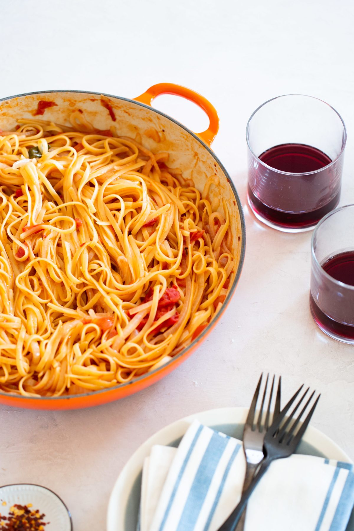 ONE PAN TOMATO AND ONION PASTA in a lecreuset pan and two glasses of red wine on the side.