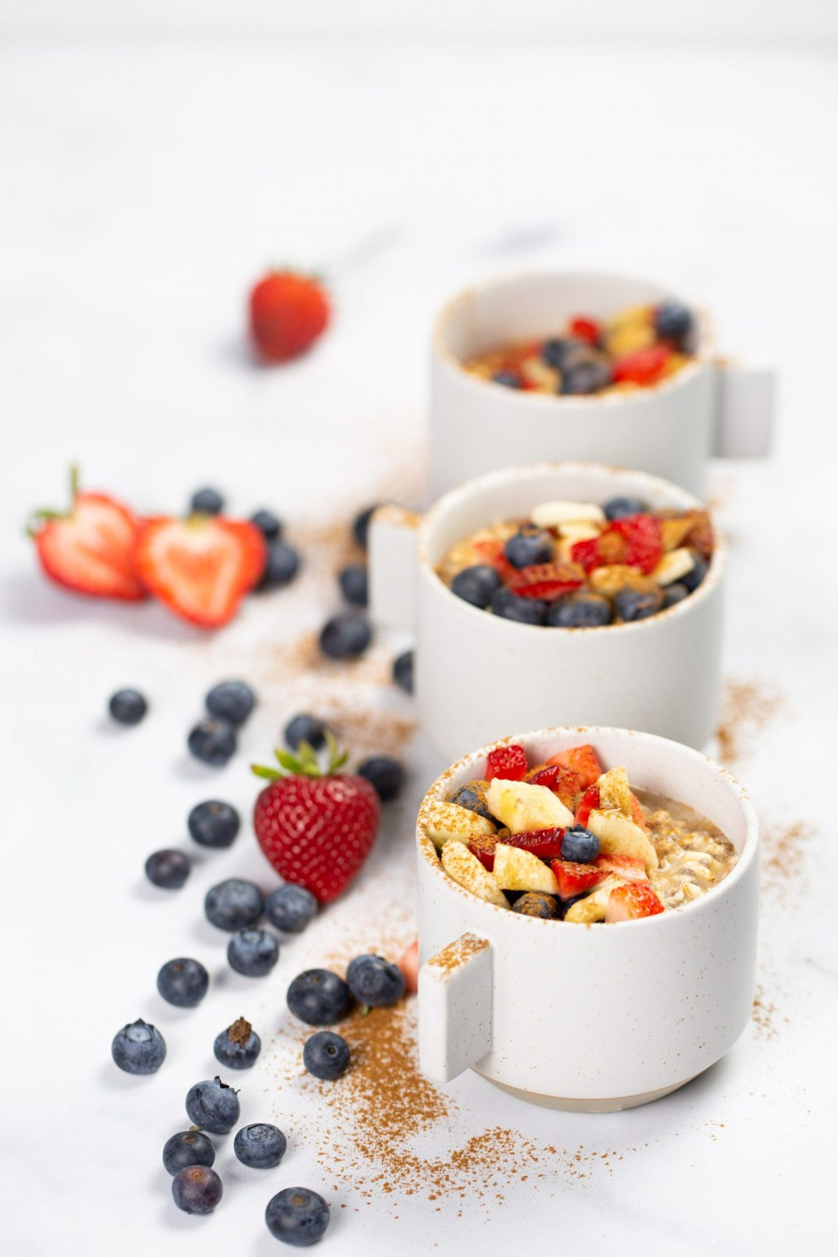 Mugs with overnight oats topped with berries and cground cinammon.