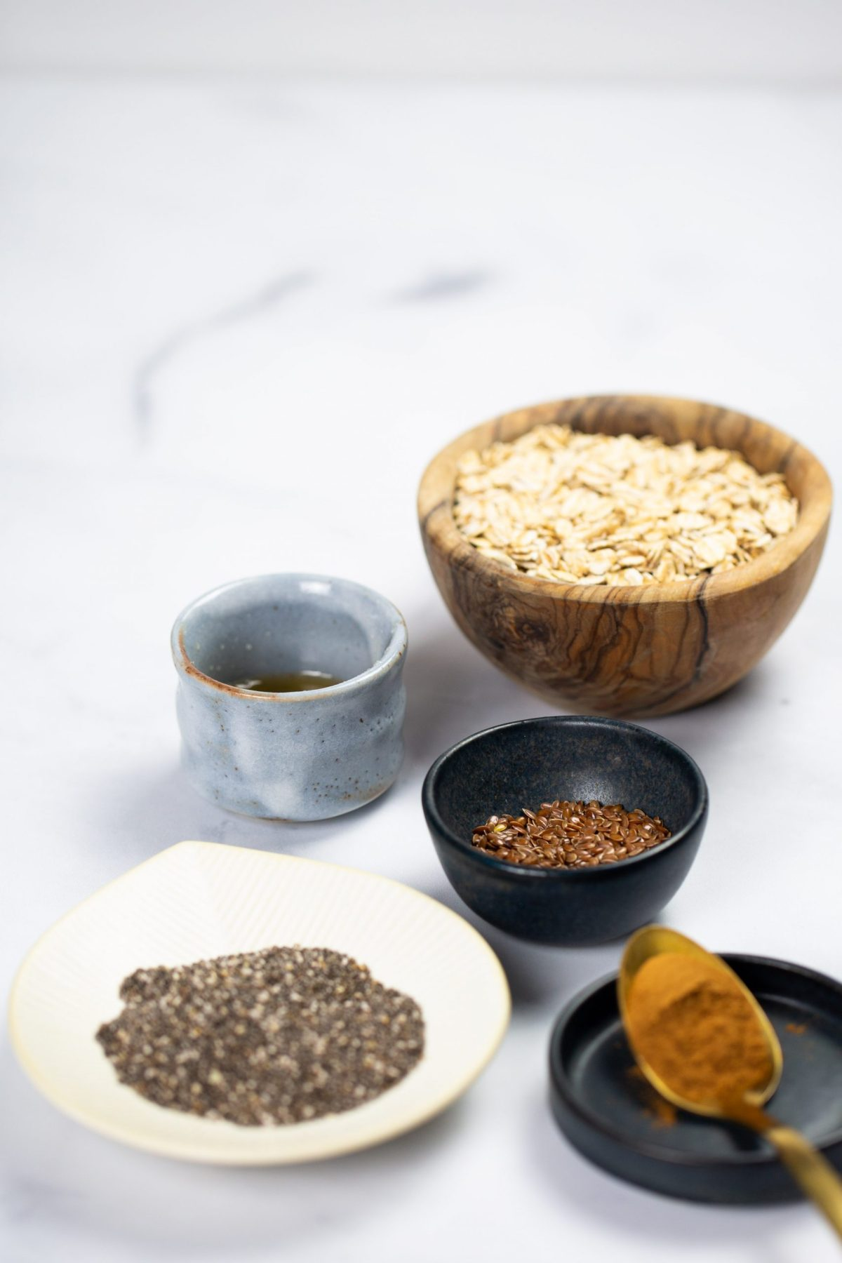 Oats, flaxseds, chia seed and other ingredients to prepare overnight oats.