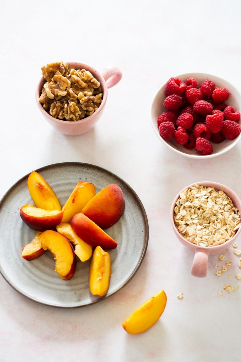 Peaches, raspberries, nuts and oats in dishes