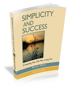 A 3-D photo of the book Simplicity and Success, by Bruce Elkin. It is standing on a table, throwing a shadow. As well as the title, there is a photo of a peace pond at sunset.