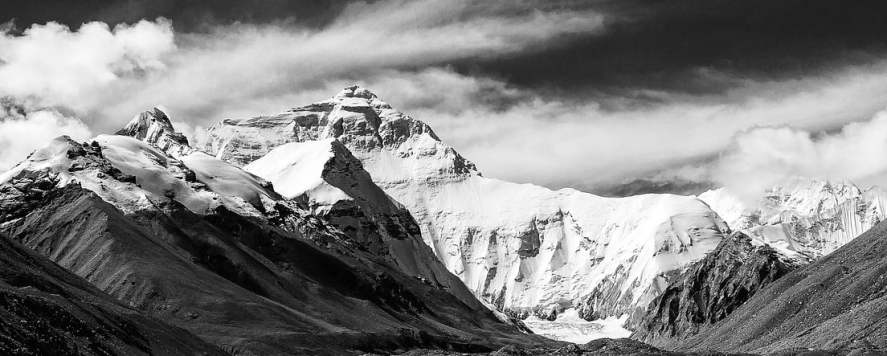 A view of Mount Everest from Tibet, lowlands in front, clouds streaming overhead