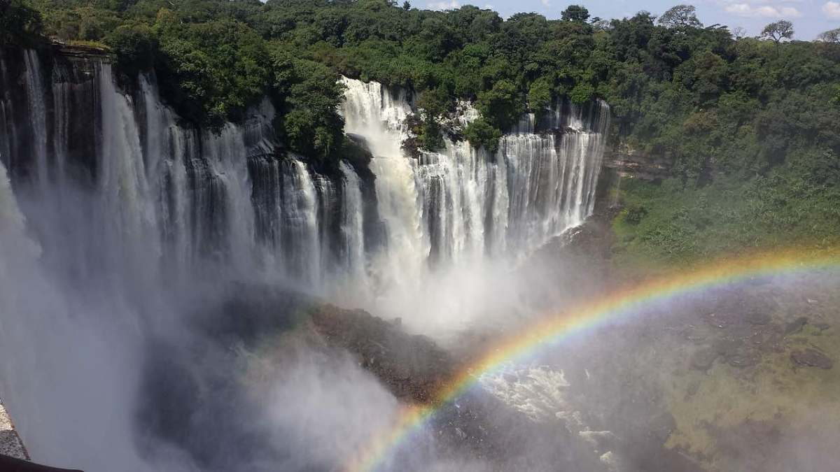 A multi-stream waterfall in a jungle with a rainbow in the mist in front of it.
