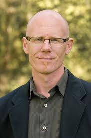 Head shot of author Stephen Legault, against a blurry green forest background