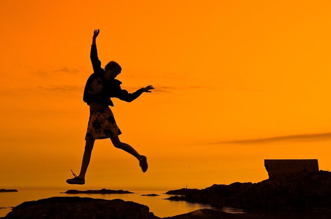 Woman jumping for joy above seashore rocks, silhouetted against a deep, rich orange sky.