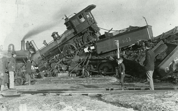 A vintage black and white photo of a train crashing into another, and both are off the tracks. People stand by watching