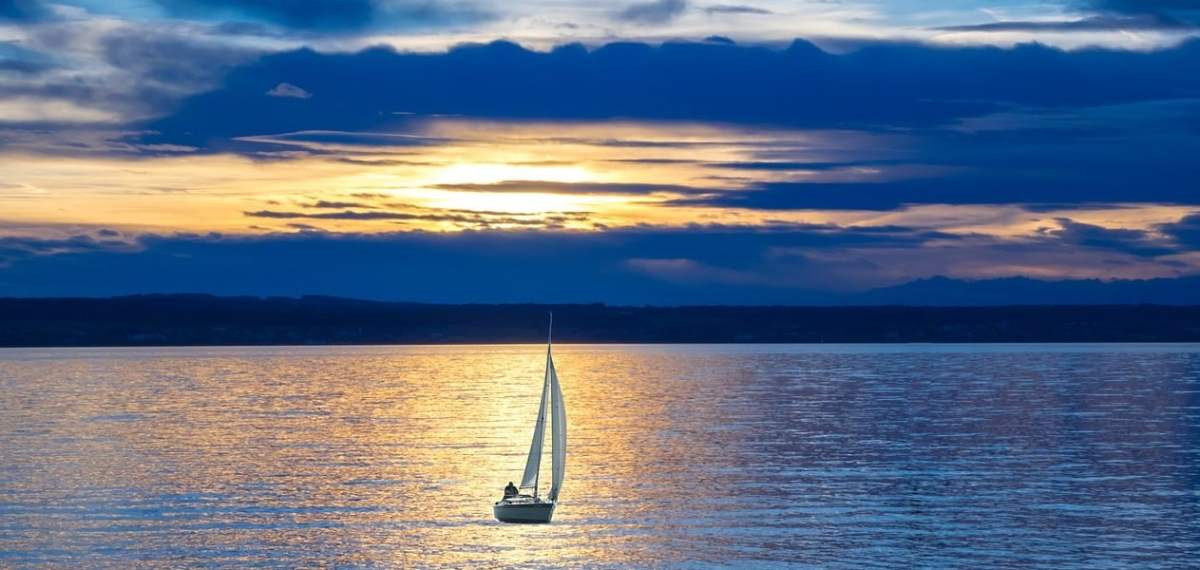 A sailboat is highlighted in a reflected path of golden light, as the sun drops below a layer of dark clouds. A visual metaphor for the path of least resistance