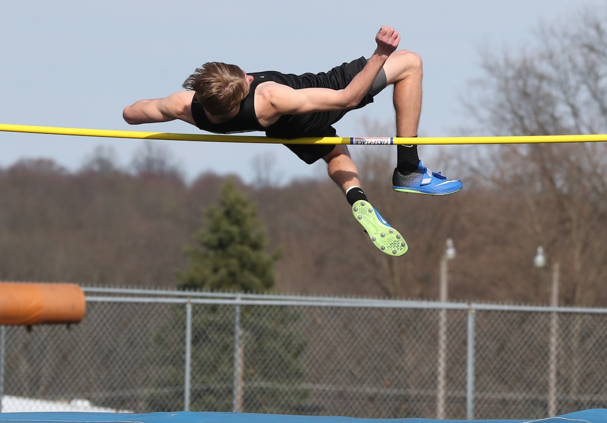 A high-jumper throws himself over a bar set high, his back almost touching the bar, and in preparation for the kick what will take him up and over.