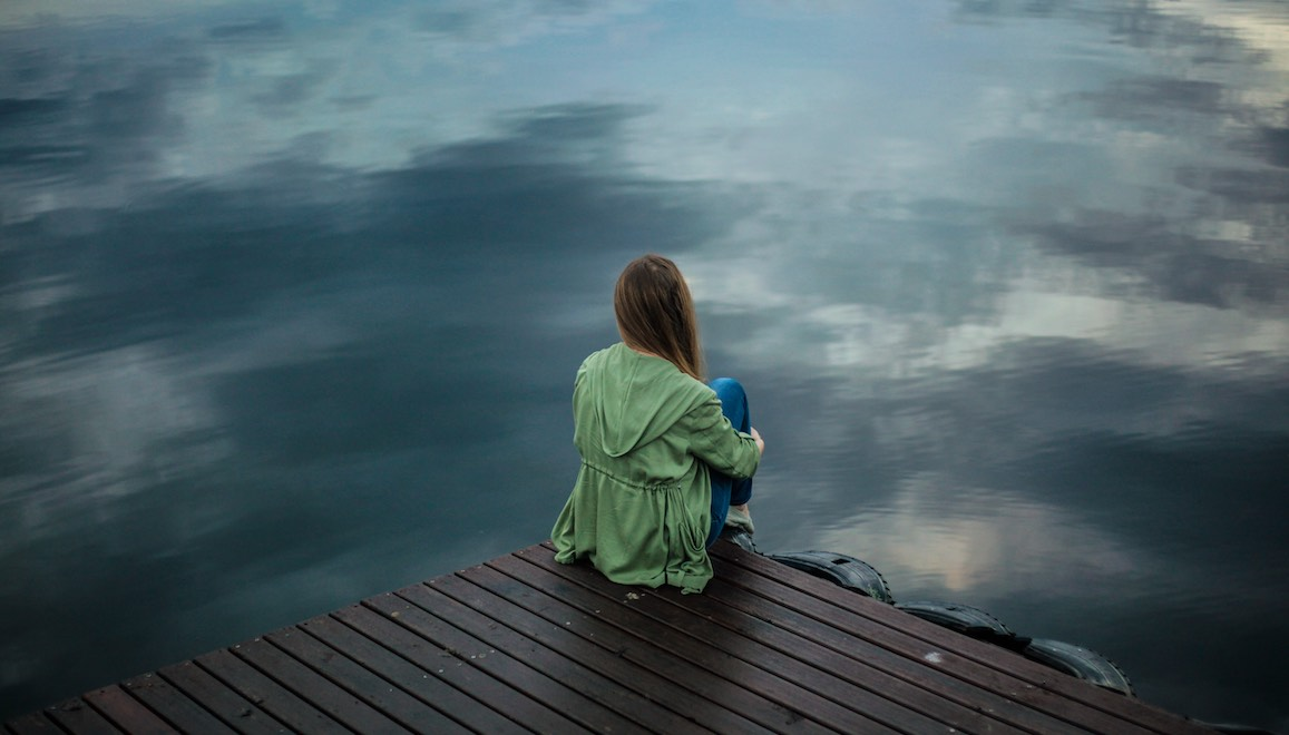 A long haired woman in a loose rain jacket sits sadly on a wooden dock with her knees pull to her chest. The water below her is different shades of grey.