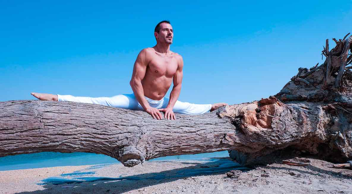 A fit-looking yoga instructor does the splits on a weathered seaside log. Blue sky behind him.