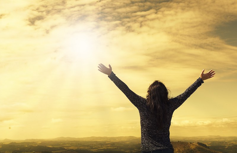 A resilient woman reaches both arms skyward as sun bursts through yellowtinted sky, after a storm.