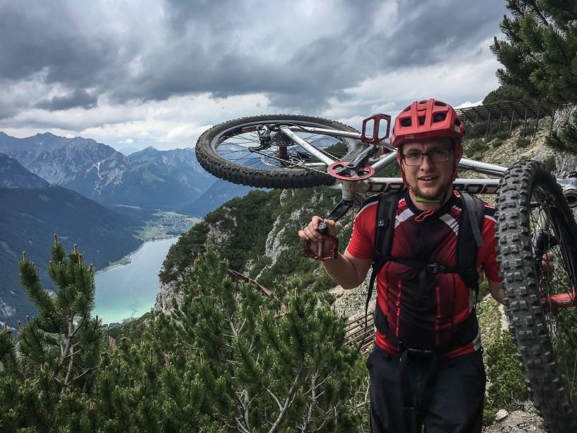 Das Bike auf der Schulter - im Hintergrund der Achensee.