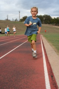 Luke runs toward the camera on a school track.