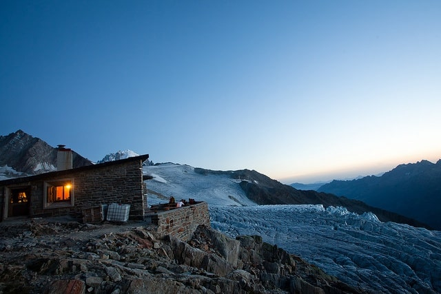 A fire glows in a cabin overlooking a wintry mountain range, perfect for rest.