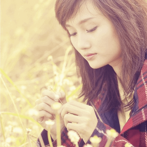 A young woman quietly prays among a field of wheat.