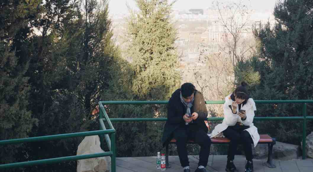 couple on phones on park bench busyness is destroying your marriage