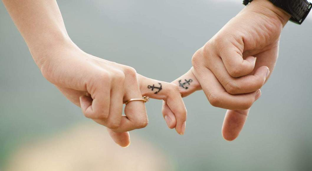 couple interlocking fingers with anchor tatoos