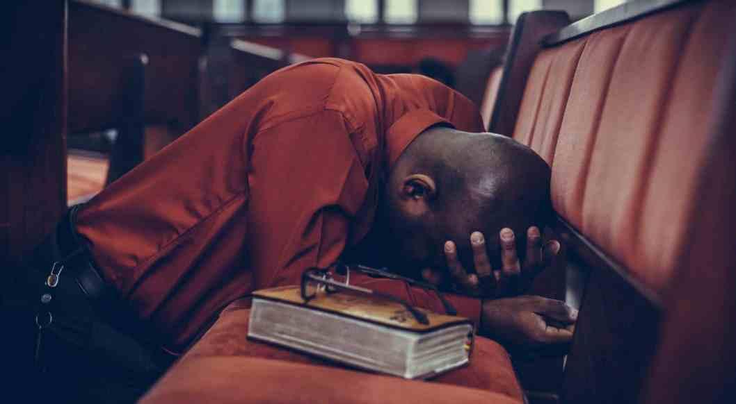 man praying with bible on pew