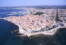 Una veduta aerea della città di Alghero, in Sardegna: meta gettonatissima da molti bresciani