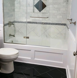 picture of a bathroom renovation that was done by brightside restoration general contractor in medina ohio with black floor tiles and white tile shower