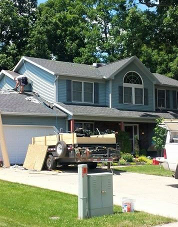 picture of a blue house showing our roofer in medina ohio putting a new roof onto a house